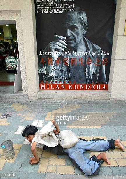 A beggar creeps under a poster promoting the wellknown Czech writer Milan Kundera's work The unbearable lightness of being at a book store in...