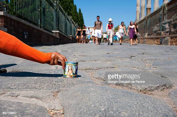 A beggar lies in the ground holding a cup with a Madonna while awaiting to collect some money from the tourists visiting the Fori Imperiali...