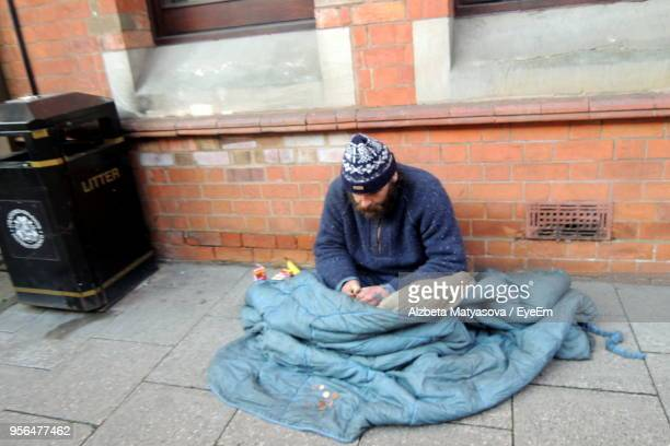 beggar man with blanket sitting by building at footpath - homelessness stock pictures, royalty-free photos & images