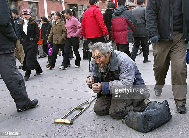 A beggar receives little attention as people celebrating the second day of the Lunar New Year holidays walk by 23 January 2004 in Beijing As China...