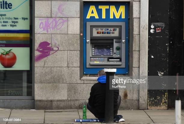 A beggar seats outside an ATM machine in Dublin City Center On Friday January 18 in Dublin Ireland