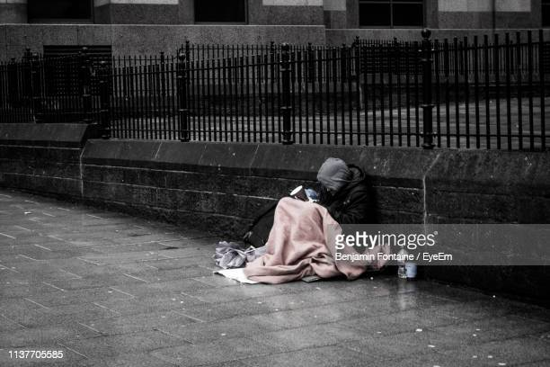 beggar sitting on street against wall - homeless foto e immagini stock