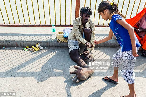 HARIDWAR UTTARAKHAND INDIA A beggar with Elephantiasis at his feet is receiving some money from a girl at Harki Pauri Ghat at the holy river Ganges