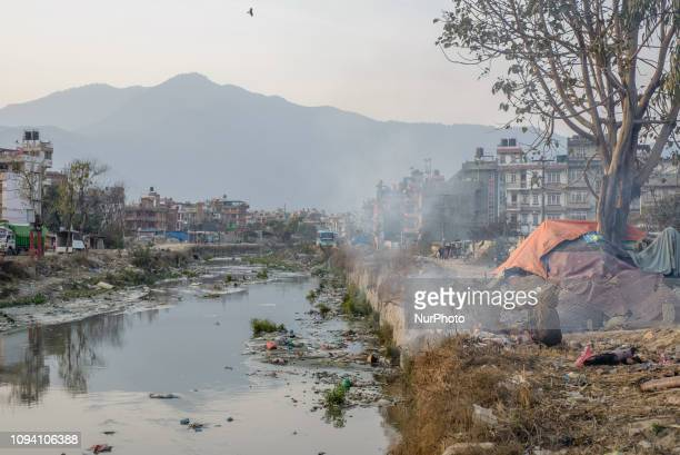 A beggar woman warms herself by the fire on the outskirts of Kathmandu Nepal on February 5 2019