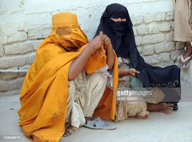 Beggars wait for alms as Pakistani men hold Friday prayers in Saudi Arabia in Larkana on September 3 2010 Relief efforts in floodravaged Pakistan are...