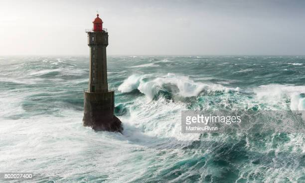begining of an amazing wave on la jument lighthouse - la jument stock pictures, royalty-free photos & images