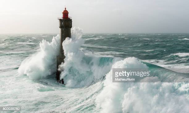begining of an amazing wave on la jument lighthouse - storm stock pictures, royalty-free photos & images