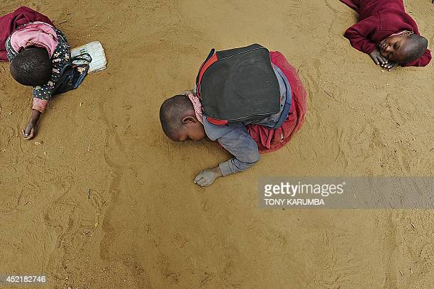 Beginners class pupils scribble notes on the ground during a lesson at the Oloserian primary school in Kajiado county some 100 kilometres south of...
