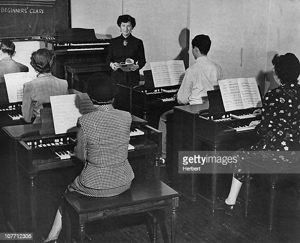 Beginners learn to play keyboards in a music class circa 1950's