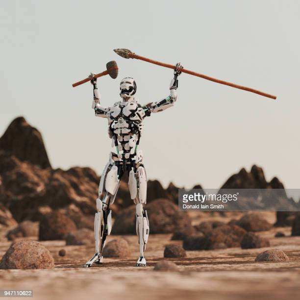 beginnings: robot rises up holding stone age weapons - stone age stock photos and pictures