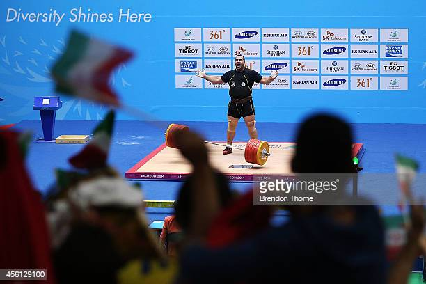 Behdad Salimikordasiabi of Iran celebrates claiming the Gold medal and breaking the Asian Games record for the Clean & Jerk in Men's +105kg...