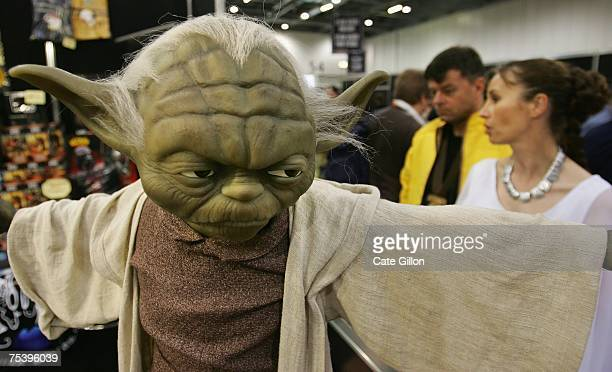 Behind a model of Yoda on display, fans dressed as Hans Solo and Princess Leia shop browse stalls at the Celebration Europe Exhibition in Excel...