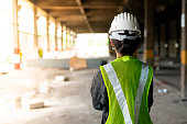 behind woman construction engineer wearing hat