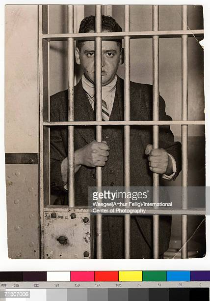 'Behind Barsfor Being a Dope' by Weegee circa 1937 The American photographer Weegee looks out from a jail cell Photo by Weegee / International Center...
