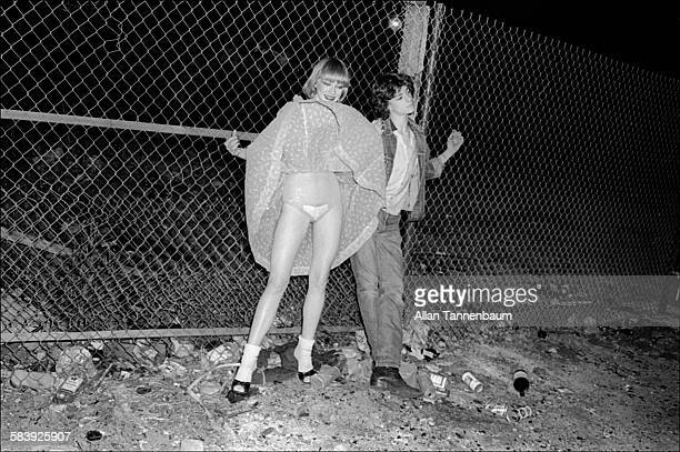 Behind CBGB on the Bowery a young woman skirt blows up around her chin as her male companion leans against a chainlink fence New York New York May 28...