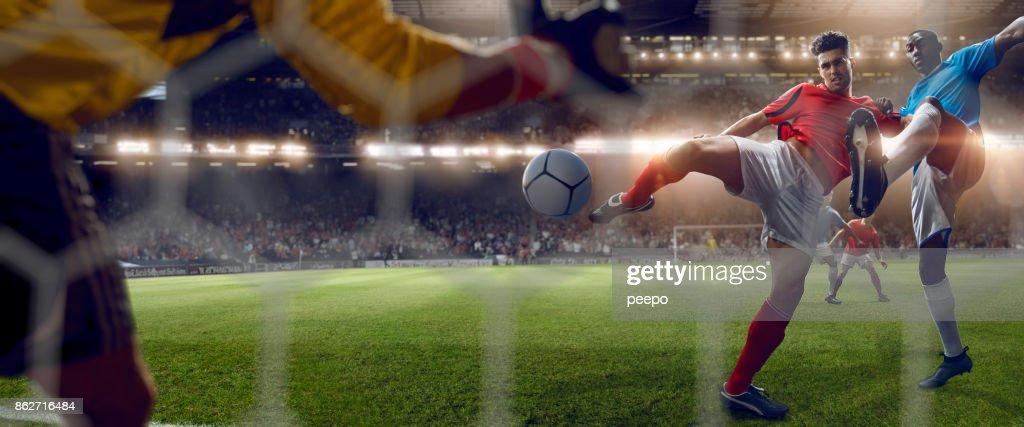 Behind Goal Net View of Footballer Volleying to Score Goal : Stock Photo