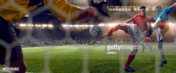 behind goal net view of footballer volleying to score goal - scoring stock pictures, royalty-free photos & images