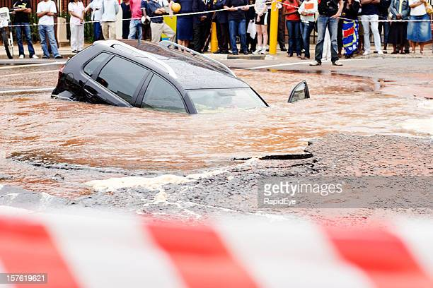 behind police cordon tape, a car slides into  muddy sinkhole - sinkhole stock photos and pictures