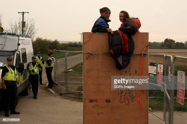 Behind the overly heavy police cordon designed to keep fellow protestors and press away two antifracking protestors smile for the photographer after...