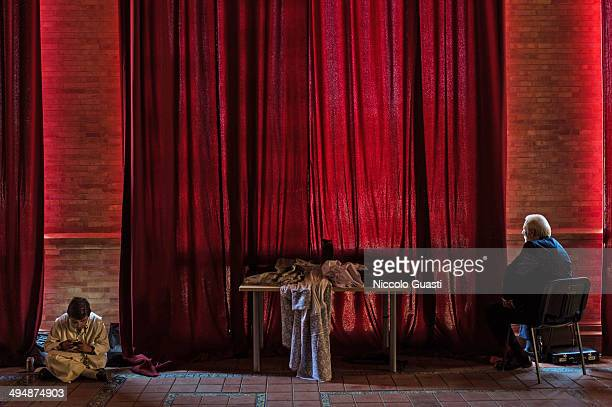 Behind the red curtain a man is glancing the ceremony as an altar boy is playing a videogame on a phone during the 50th Anniversary of 'La Macarena'...