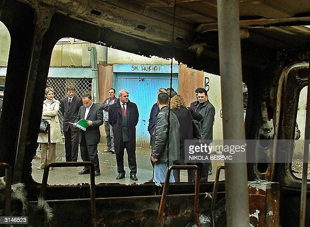 Behind the remains of a burned bus that was taking Serb pupils to school Kosovo Prime minister Bajram Rezhepi looks at a project for reparations to a...