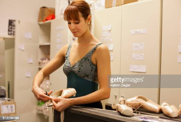 Behind the scenes at the Bavarian State Ballet: Dancer at pointe shoe department preparing her shoes