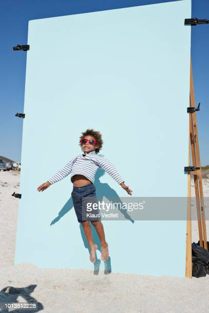 behind the scenes shot of cool boy jumping on beach with backdrop - blue shorts stock pictures, royalty-free photos & images