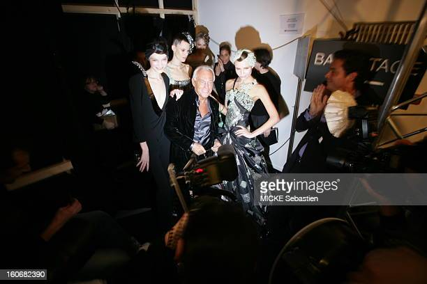Behind the scenes smiling attitude of Giorgio Armani posing with mannequins presenting the models of his haute couture line 'Prive' with dresses and...