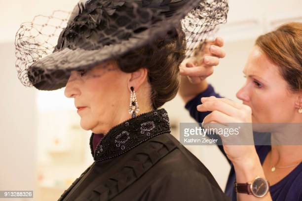 Behind the scenes: Stylist making the final touch on woman's hair before dress rehearsal