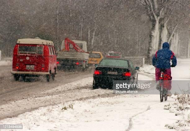 Bei dichtem Schneetreiben bahnen sich Autofahrer und Fahrradfahrer am in Essen den Weg über rutschige Straßen und Wege. Dichter Schneefall hatte fast...