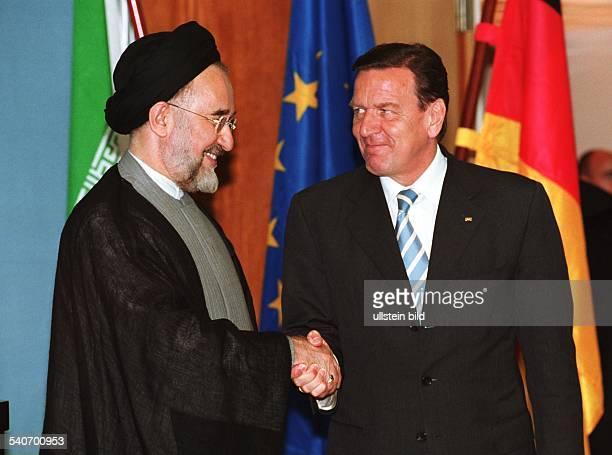 Bei seinem Besuch in Berlin schüttelt der Präsident des Iran Mohammed Khatami Bundeskanzler Gerhard Schröder die Hand. Im Hintergrund Flaggen der...