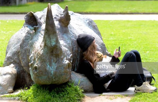 Bei Sonnenschein, leichter Bewölkung und Temperaturen um die 16 Grad sitzt ein junges Mädchen mit ihrem Handy am in Düsseldorf im Ehrenhof neben der...