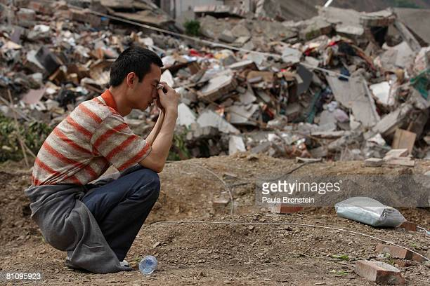 Beichuan quake survivor grieves as he tries to find family members in the rubble in the quake ravaged town where thousands are dead or missing May 15...