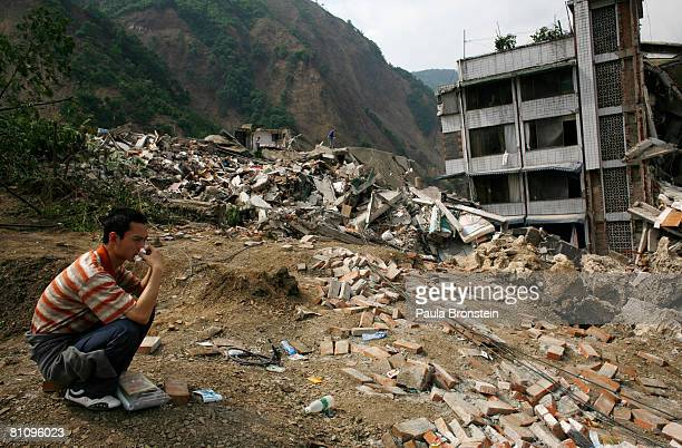 Beichuan quake survivor pauses as he tries to find family members in the rubble in the quake ravaged town where thousands are dead or missing May 15...