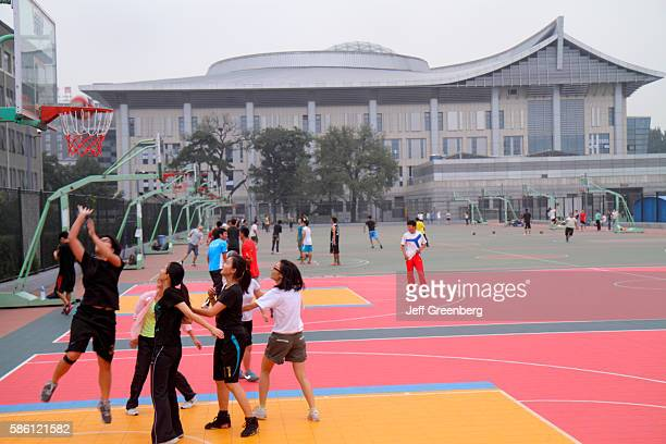 Beidˆ higher education campus Asian teen girl friends practicing on basketball court