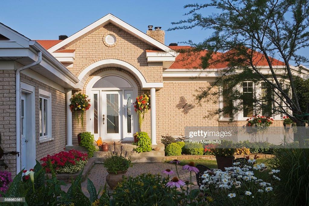 Beige brick house exterior with front door portico and flower bed garden  Stock Photo & Beige Brick House Exterior With Front Door Portico And Flower Bed ... pezcame.com