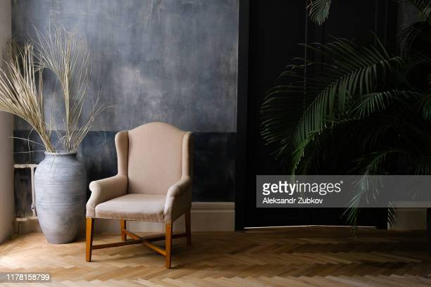 beige chair and a large vase near the window in the hall, next to a palm tree near the door. - indoors ストックフォトと画像