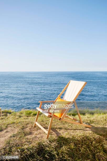 beige deckchair with orange colored pillow on meadow against sea and blue sky - ピレネーアトランティーク ストックフォトと画像