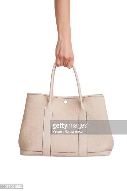beige leather handbag in woman's hand isolated on white background - clutch bag stock pictures, royalty-free photos & images