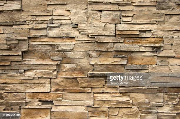 beige sandstone tiles on a surrounding wall - sandstone stock pictures, royalty-free photos & images