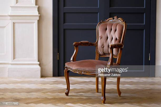beige velour chair against the black doors in the living room. the interior of the room in retro style. - antique stock pictures, royalty-free photos & images