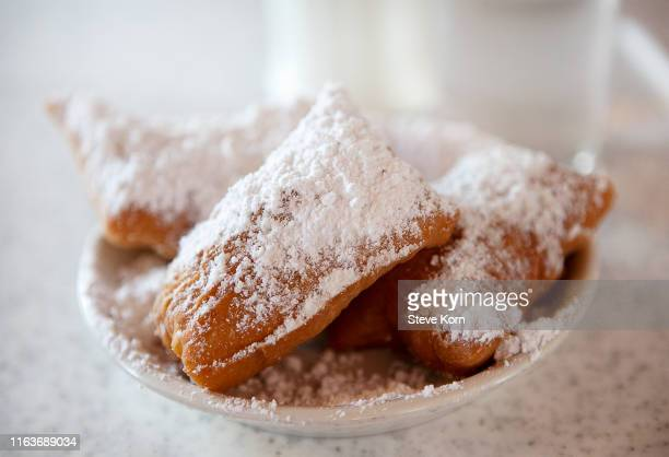 beignets with powdered sugar on plate - new orleans stock pictures, royalty-free photos & images