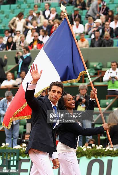 Beijing 2008 Olympic flag-bearer Tony Estanguet waves to the crowd as the London 2012 Olympic flag-bearer Laura Flessel holds the French national...