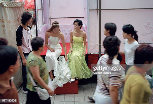 Beijing A City Transforming Behind screens on a busy street fashion models wait to take part in a weddingdress fashion show The show is being held in...