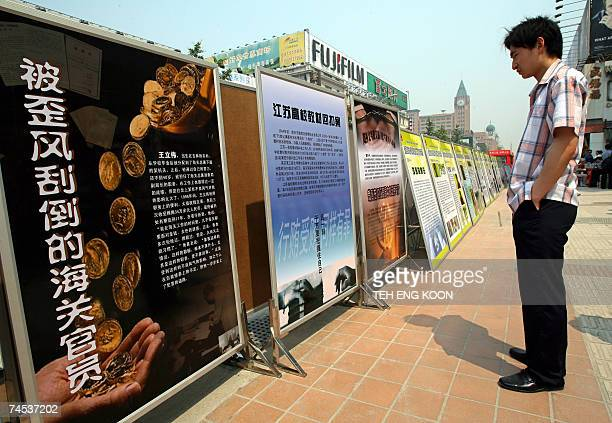A Chinese man looks at anti corruption billboards on display in Central Beijing 11 June 2007 Unable to stem a rising tide of corruption China is now...