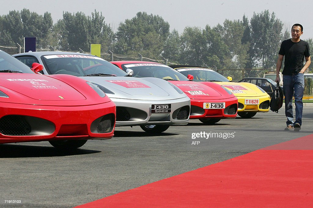 A Chinese Man Walks By Ferrari Cars Lined Up Outside The Newly Opened  Ferrari Showroom In