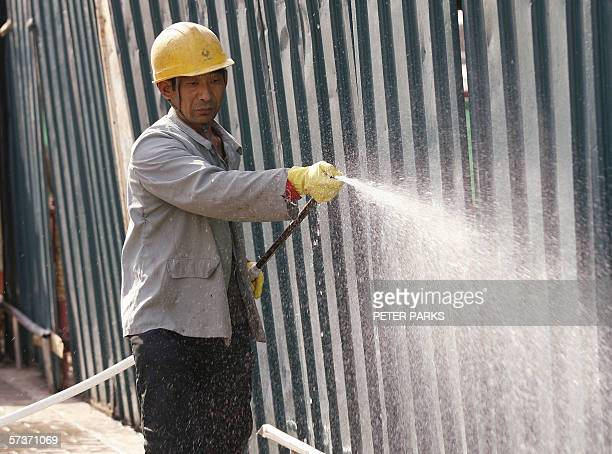 Construction worker hoses down dust on a building site in Beijing, 20 April 2006. China's booming economy grew 10.2 percent in the first quarter,...