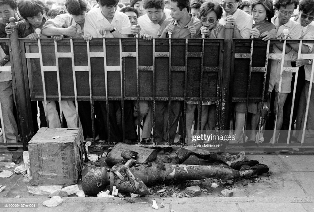 Crowd looking at burnt body of soldier (B&W) : News Photo