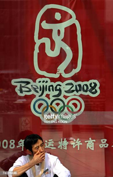A man smokes a cigarette in front of the Beijing 2008 Olympic games logo on display in central Beijing 30 April 2007 According to Amnesty...