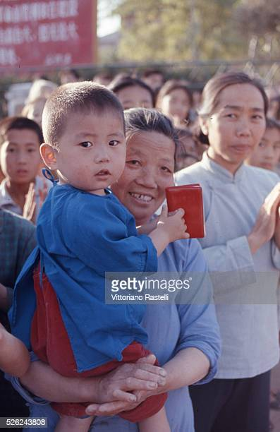 Beijing China A mother holds in her arms her child attending a nursery school and he holds Mao Zedongs Red Book in Beijing May 21 1971